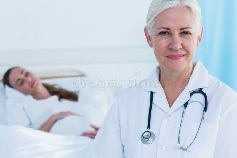 Download Docteur Féminin Souriant à L'appareil-photo Tandis Que Son Sommeil Patient Photo stock - Image du ventre, prévoir: 56481444