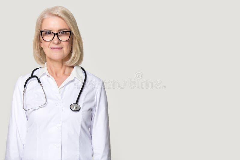 Docteur féminin supérieur attirant posant sur le fond gris de studio photo stock