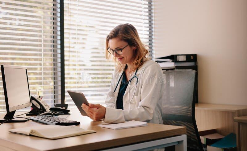 Docteur féminin travaillant sur son PC de comprimé images stock