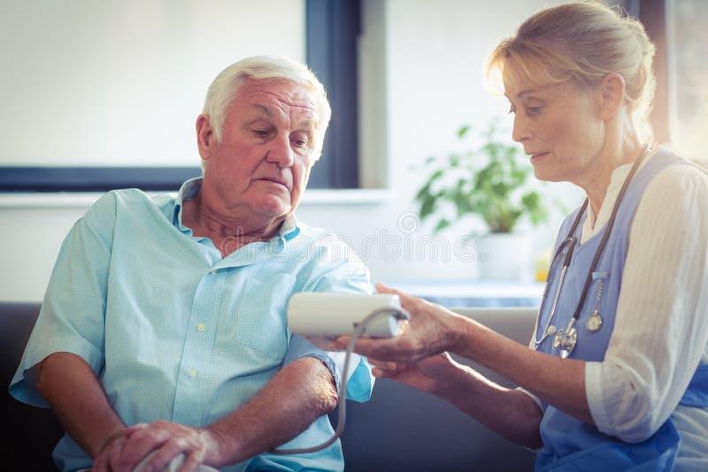 Docteur féminin vérifiant la tension artérielle de l'homme supérieur image stock