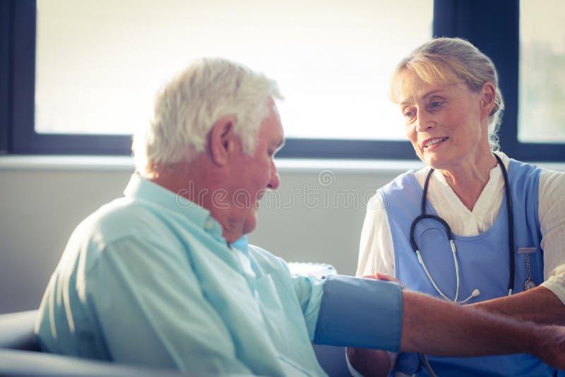 Docteur féminin vérifiant la tension artérielle de l'homme supérieur photo libre de droits