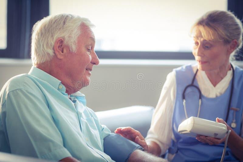 Docteur féminin vérifiant la tension artérielle de l'homme supérieur image libre de droits