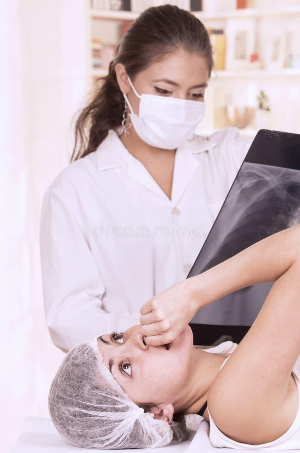 Docteur féminin vérifiant le rayon X d'une jeune fille photographie stock