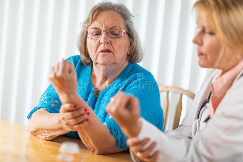 Docteur f?minin Talking avec la femme adulte sup?rieure au sujet de la th?rapie de main images libres de droits