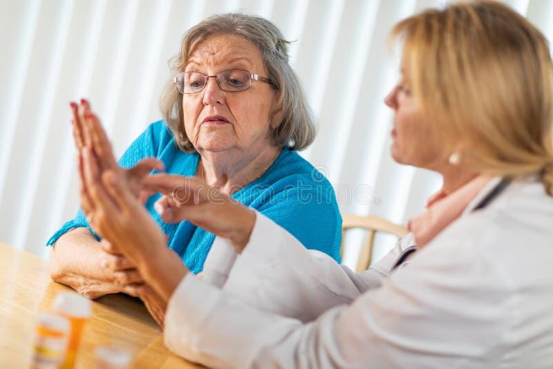 Docteur f?minin Talking avec la femme adulte sup?rieure au sujet de la th?rapie de main image stock