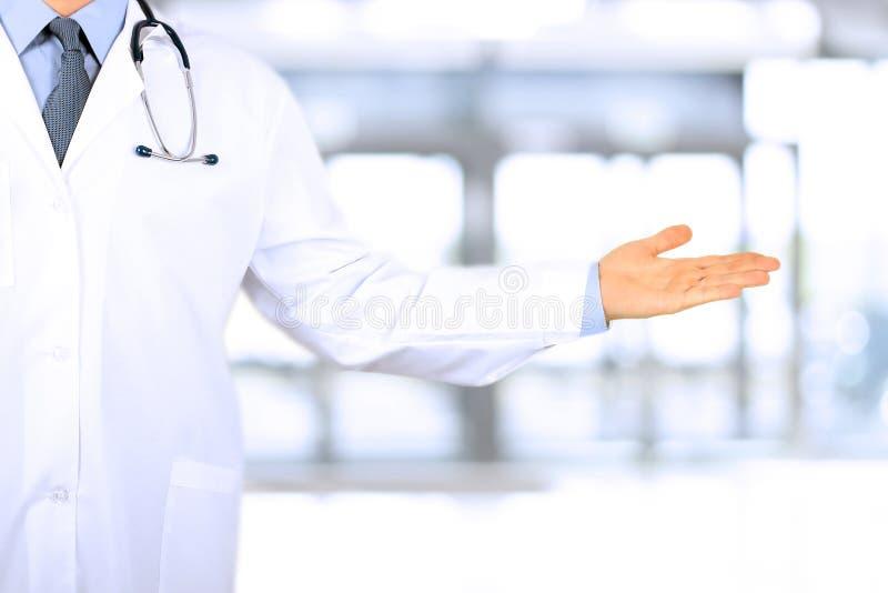 Docteur faisant de la publicité votre produit soignez le pointage parti tout en se tenant sur le fond gris photographie stock