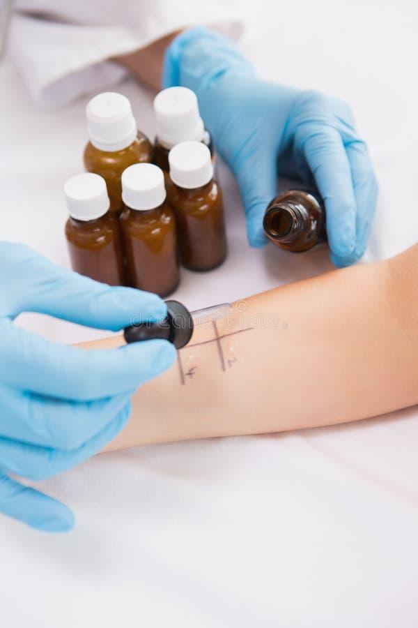 Docteur faisant l'essai de piqûre de peau à son patient image libre de droits