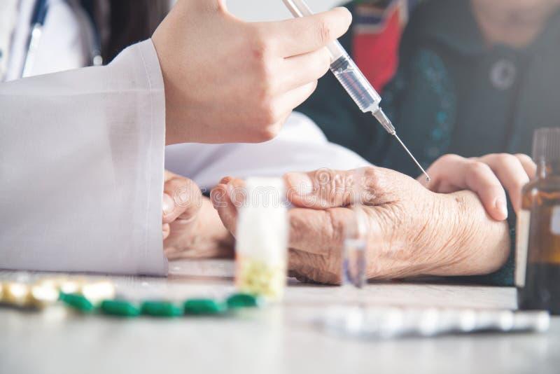 Docteur faisant l'injection chez la femme agée photos libres de droits