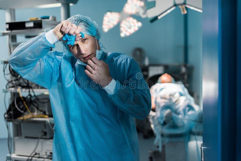docteur fatigué enlevant le masque médical et le front émouvant photographie stock