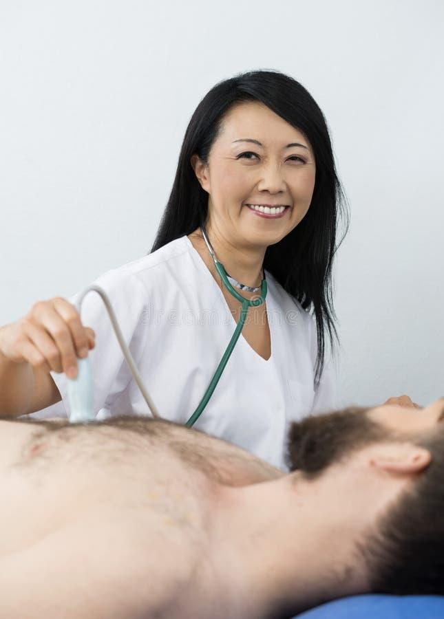 Docteur heureux Performing Ultrasound Test sur le patient images libres de droits