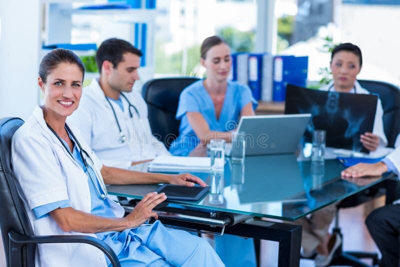 Download Docteur Heureux Regardant L'appareil-photo Avec Des Collègues Derrière Image stock - Image du confiant, caucasien: 56482023