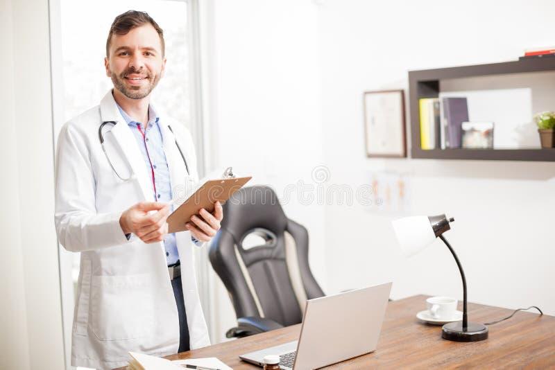 Docteur hispanique te souhaitant la bienvenue dans son bureau photos stock