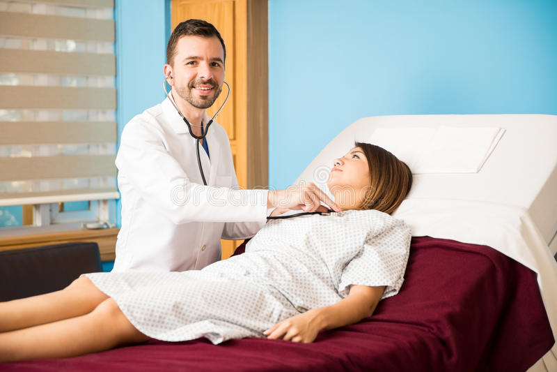 Docteur hispanique vérifiant ses patients photo stock