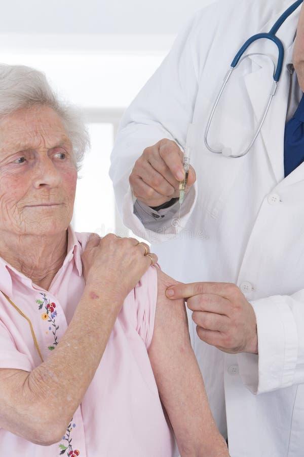 Docteur injectant le vaccin à la femme photos stock