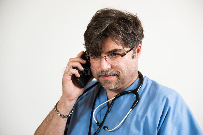 Docteur intéressé au téléphone portable images stock