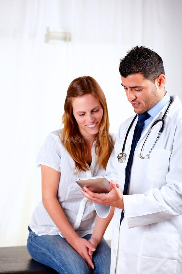 Docteur latin et une femelle regardant pour marquer sur tablette le PC images libres de droits