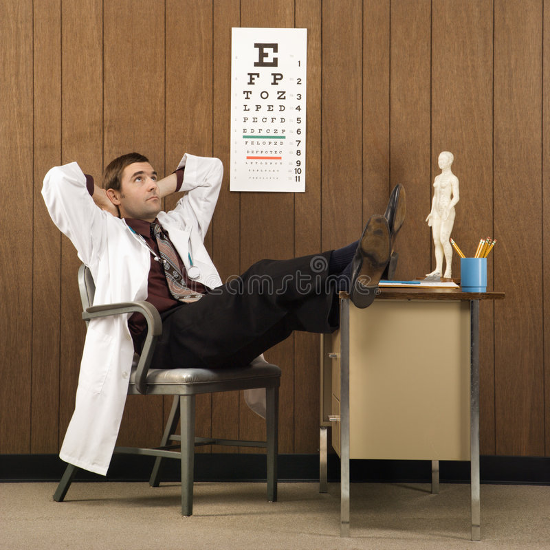Docteur mâle avec des pieds sur le bureau images libres de droits