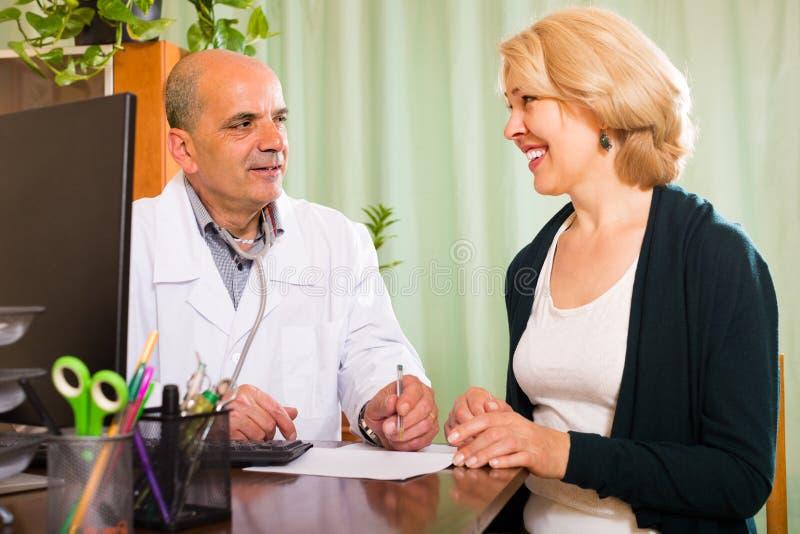 Docteur mâle avec le patient féminin photo stock