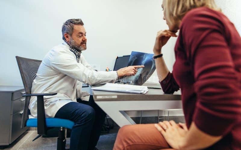 Docteur mûr discutant le résultat de balayage médical avec le patient photo stock