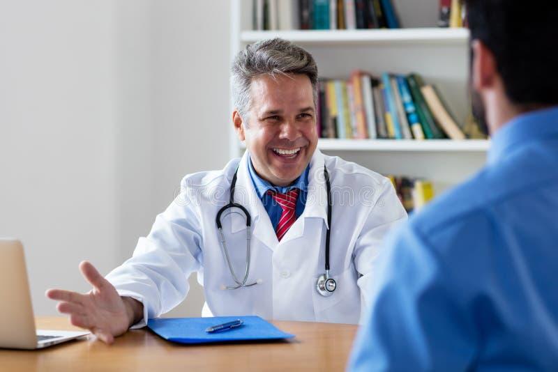 Docteur mûr riant avec de bonnes nouvelles pour le patient image stock