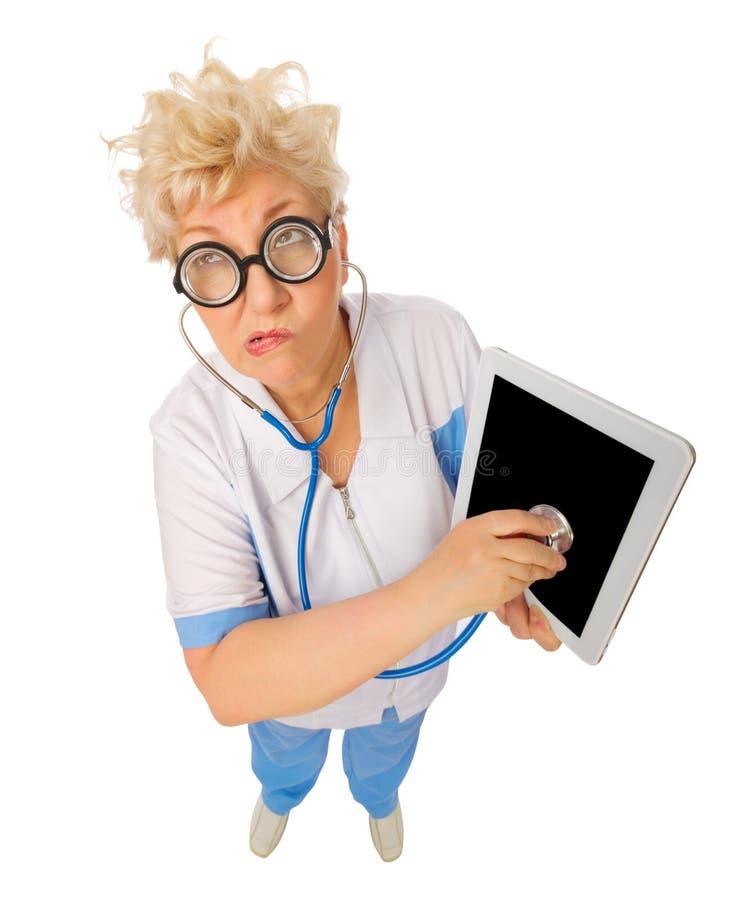 Docteur mûr drôle avec le PC de comprimé photographie stock