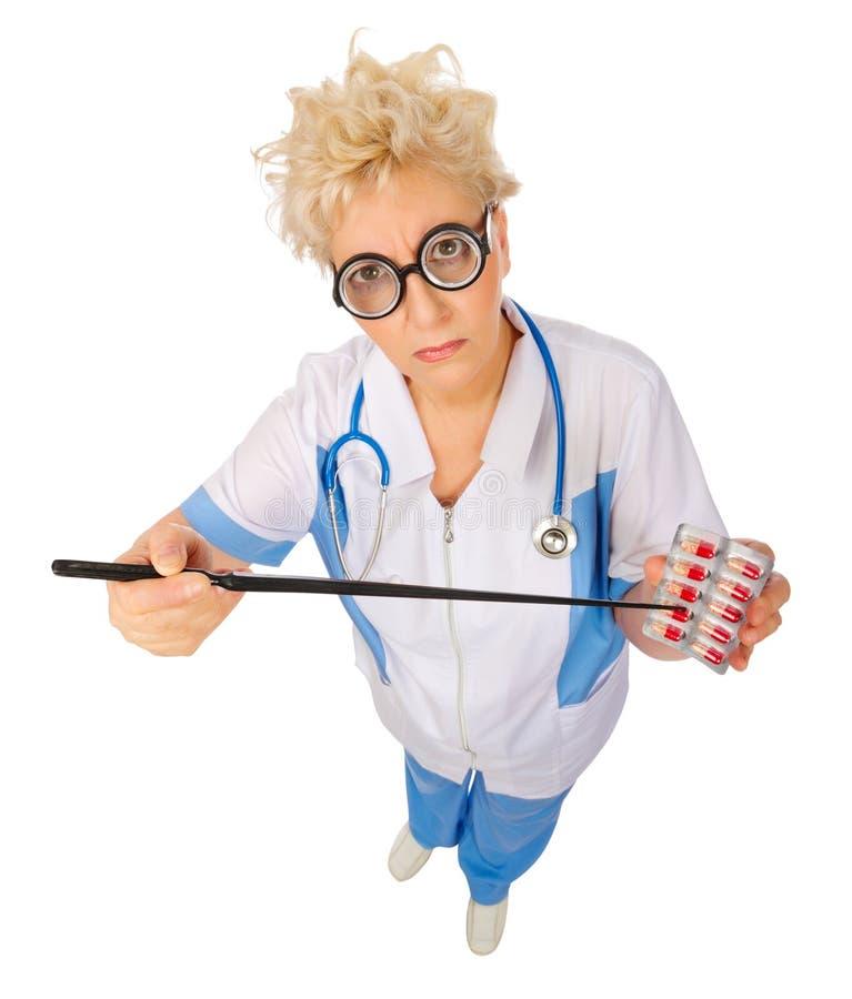 Docteur mûr drôle avec les pilules et l'indicateur photos libres de droits