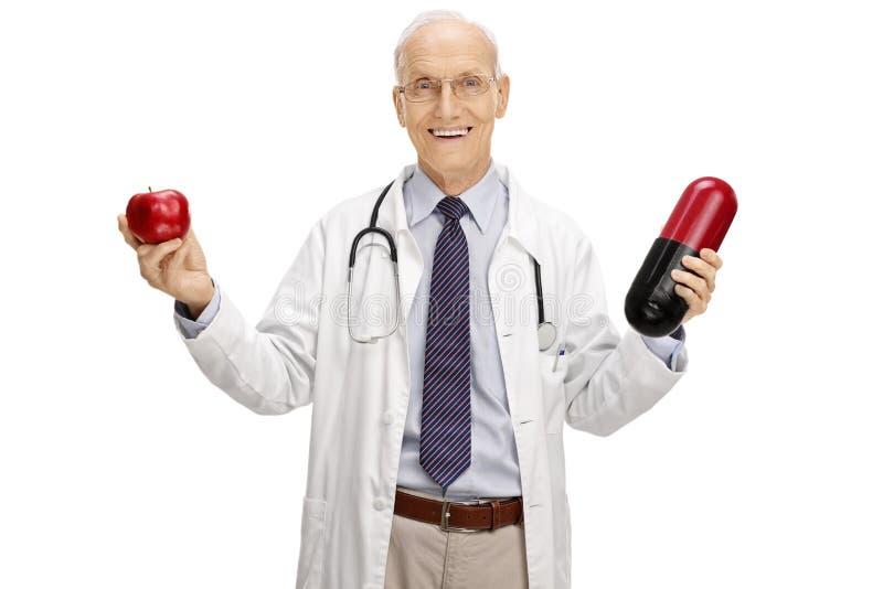 Docteur mûr joyeux tenant une pomme et une grande pilule photos libres de droits