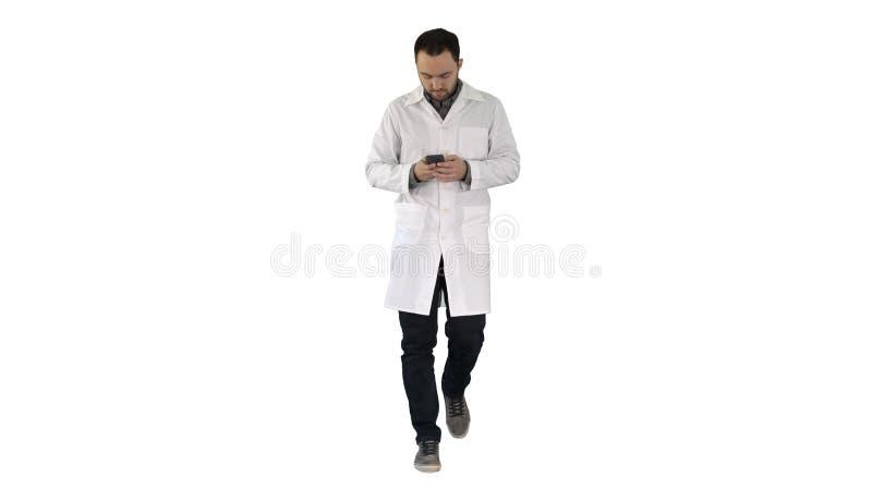 Docteur marchant et ?crivant un message au t?l?phone sur le fond blanc photo libre de droits