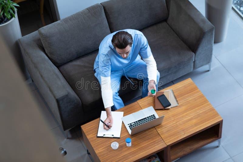 Docteur masculin écrivant sur le presse-papiers dans le lobby d'hôpital photo stock
