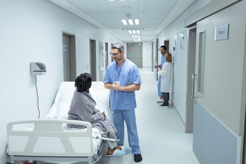 Docteur masculin agissant l'un sur l'autre avec le patient féminin handicapé dans le couloir photos libres de droits