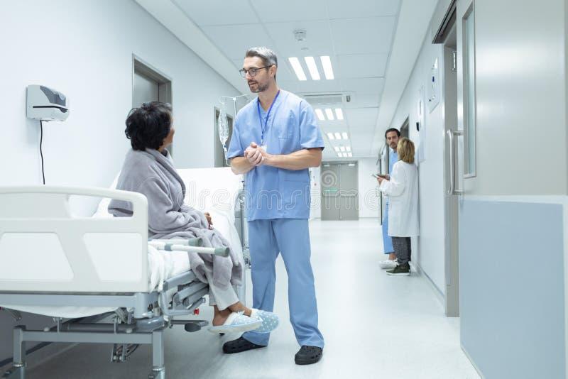 Docteur masculin agissant l'un sur l'autre avec le patient féminin handicapé dans le couloir photo stock