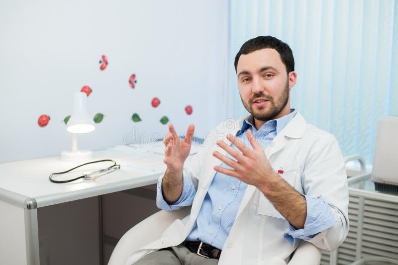 Docteur masculin amical de therapeutist de médecine s'asseyant dans le bureau, parler patient et regarder à l'appareil-photo Aide photo libre de droits