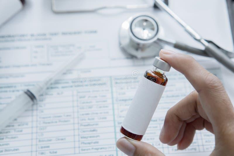 Docteur masculin anonyme tenant une fiole de médecine images libres de droits