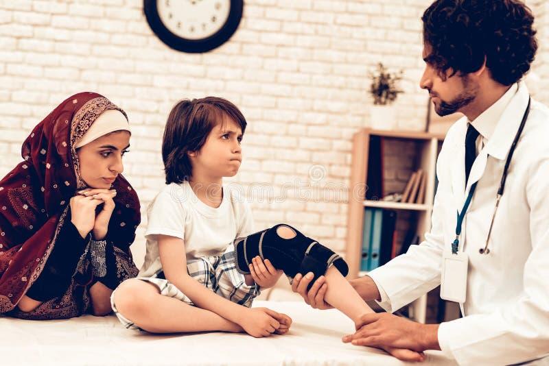 Docteur masculin arabe Bandaging Leg Injury d'enfant Concept d'hôpital Concept sain Docteur de visite patient d'enfant Docteur photos libres de droits
