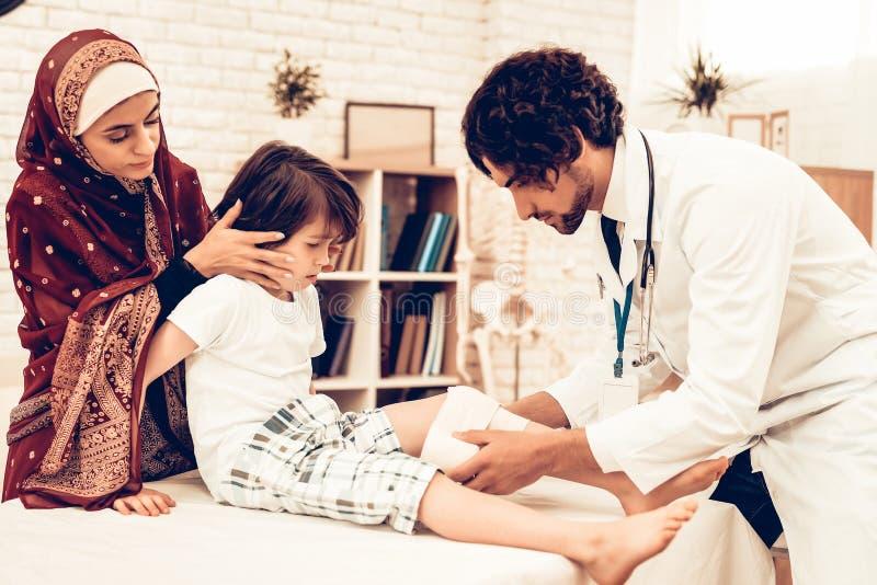 Docteur masculin arabe Bandaging Limb de patient d'enfant Concept d'hôpital Concept sain Docteur de visite patient d'enfant Docte photos stock