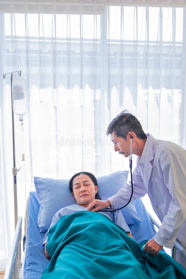 Docteur masculin asiatique supérieur visitant et contrôler le patient féminin d'une cinquantaine d'années sur la salle dans l'hôp photos libres de droits
