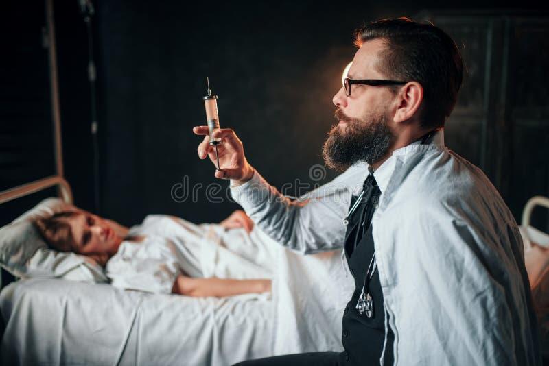 Docteur masculin avec la seringue contre la femme malade dans le lit photo libre de droits