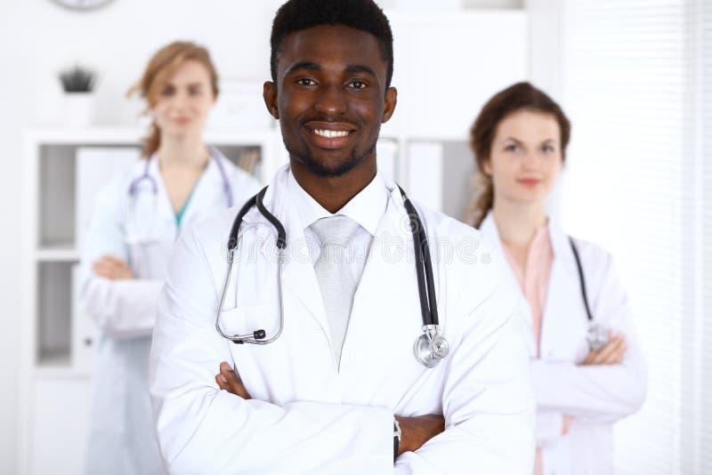 Docteur masculin d'afro-américain heureux avec le personnel médical à l'hôpital stéthoscope réglé d'argent de médecine de mensong photos libres de droits