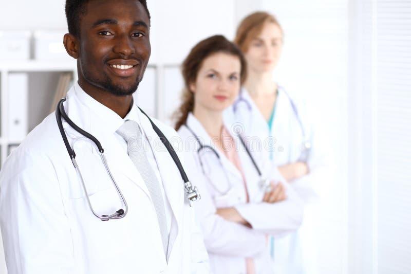 Docteur masculin d'afro-américain heureux avec le personnel médical à l'hôpital stéthoscope réglé d'argent de médecine de mensong image libre de droits