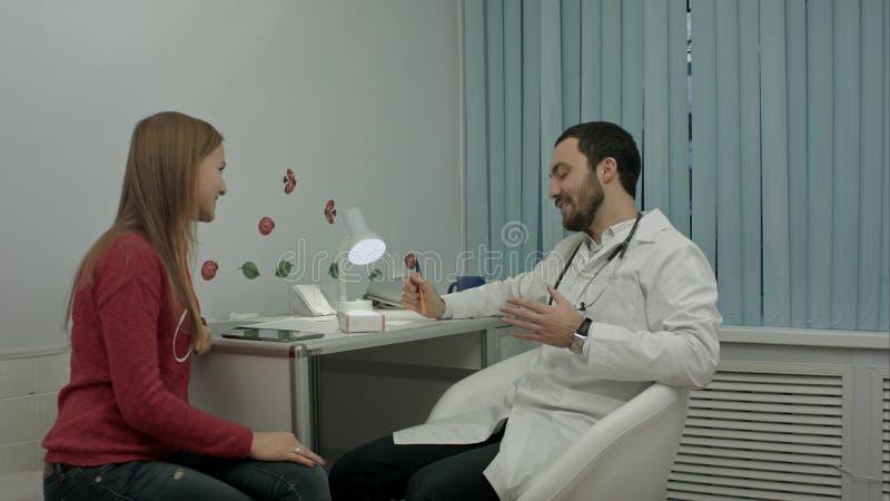 Docteur masculin dans la clinique donnant le reccomendation au patient au sujet des pilules image stock
