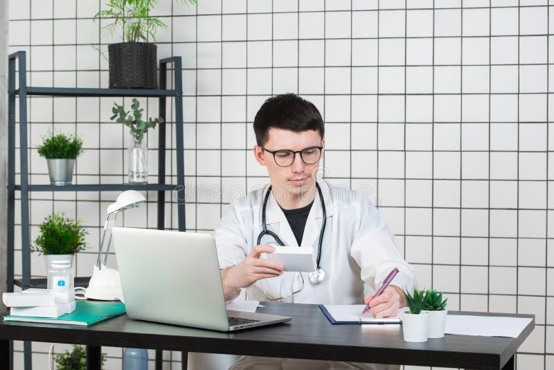 Docteur masculin dans le manteau blanc avec le stéthoscope au-dessus de son cou se reposant à la table pensant sur la prescriptio photo libre de droits