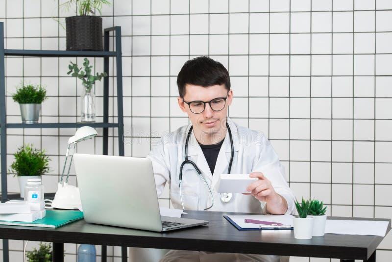 Docteur masculin dans le manteau blanc avec le stéthoscope au-dessus de son cou se reposant à la table pensant sur la prescriptio image stock