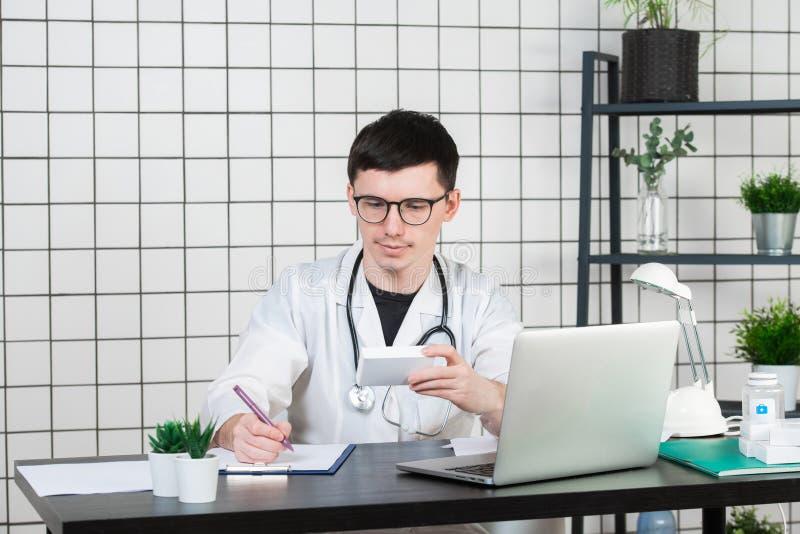 Docteur masculin dans le manteau blanc avec le stéthoscope au-dessus de son cou se reposant à la table pensant sur la prescriptio photos stock
