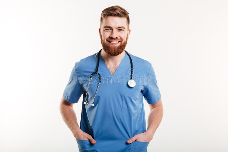 Docteur masculin de sourire se tenant avec le stéthoscope et tenir des mains dans des poches photo stock