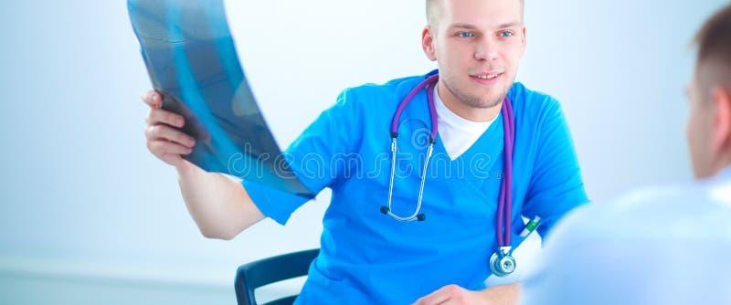 Docteur masculin expliquant le rayon X d'épine au patient dans le bureau médical photo libre de droits