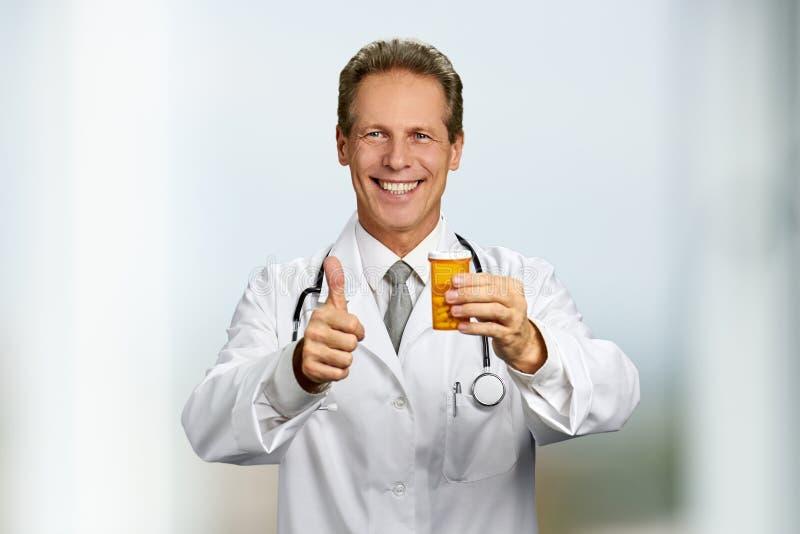 Docteur masculin gai montrant le pouce  images stock