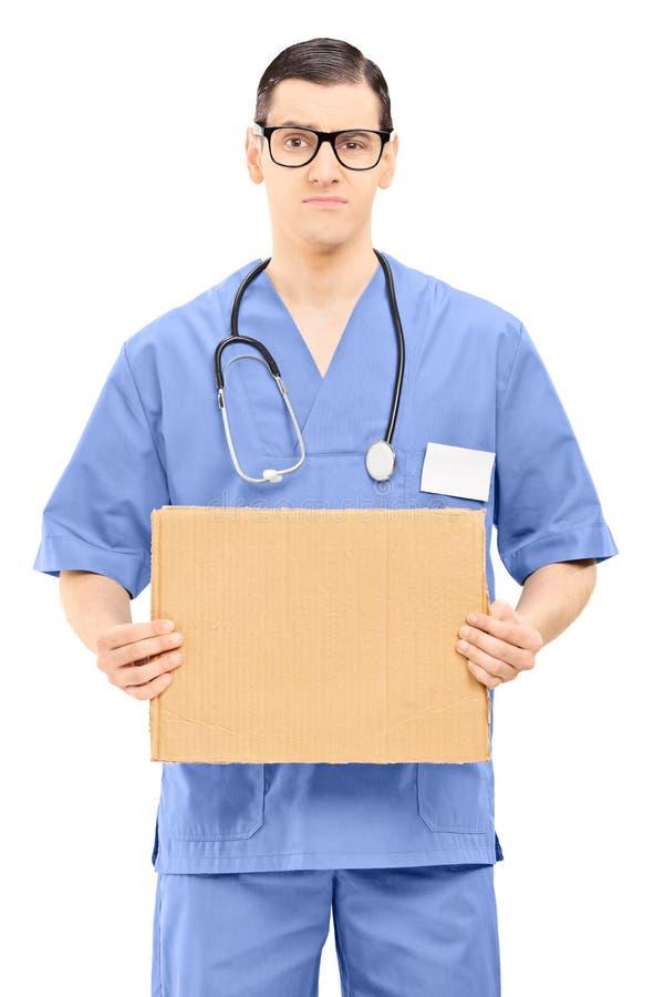 Docteur masculin grincheux tenant un signe de bande dessinée photographie stock libre de droits
