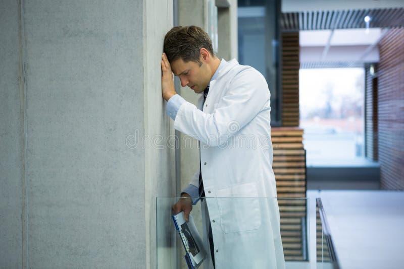 Docteur masculin inquiété se penchant sur le mur près du couloir images stock
