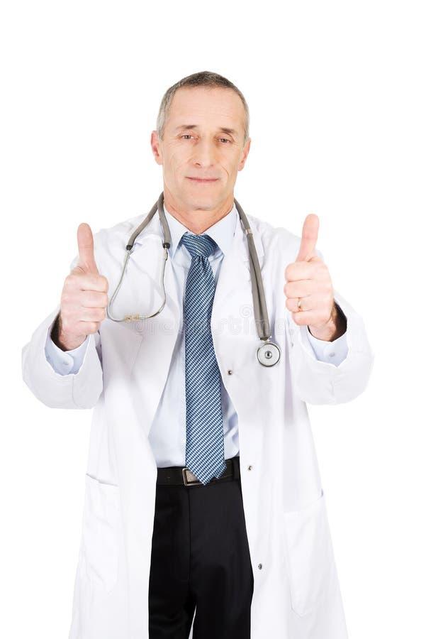 Docteur masculin mûr avec des pouces  image stock