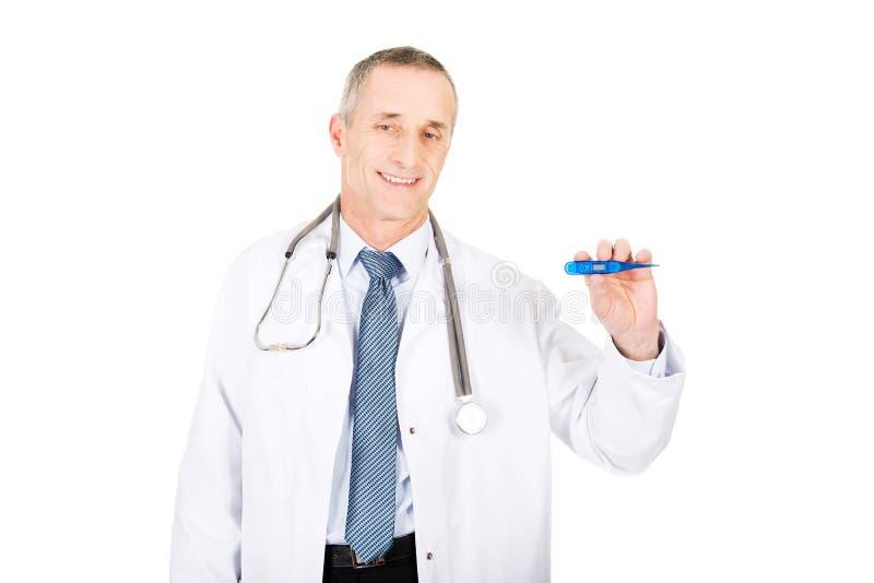 Docteur masculin mûr tenant un thermomètre images stock